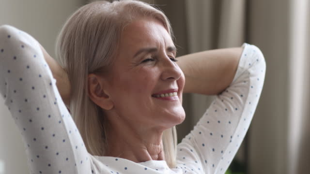 Happy dreamy older woman relax hands behind head at home Happy relaxed dreamy middle aged older woman relax hold hands behind head sitting at home, calm mature adult lady smiling face rest dream alone enjoy comfort stress free peace of mind, close up view satisfaction stock videos & royalty-free footage