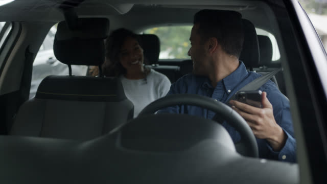 Happy driver from a car request service driving a black beautiful woman