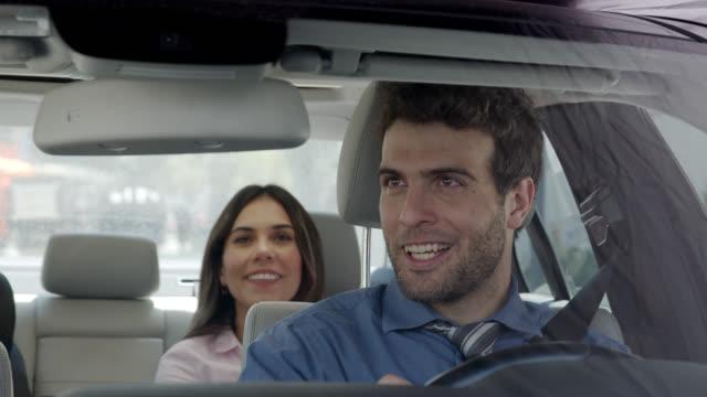vídeos y material grabado en eventos de stock de conductor feliz que transporta a una mujer de negocios mientras habla y sonríe - uso compartido del coche