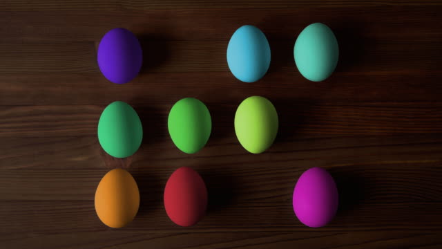 Happy easter! Colorful eggs for Easter on wooden background. Stop Motion.