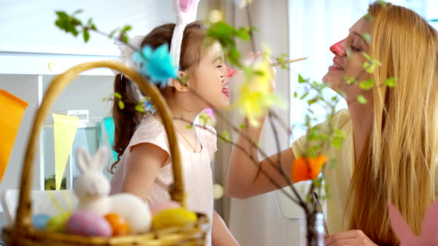 Happy Easter! Mother and her daughter having fun and paint each other's Bunnies faces