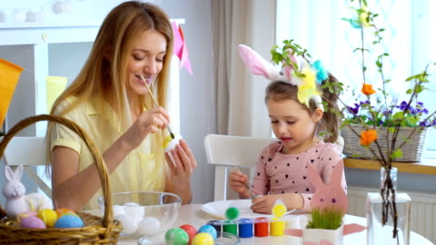Happy Easter! Mother and her little daughter wearing funny rabbit ears coloring easter eggs Happy Easter! Young mother and her cute little daughter wearing funny rabbit ears are coloring easter eggs sitting at a festive table with basket and Bunny. Slow Motion craft stock videos & royalty-free footage