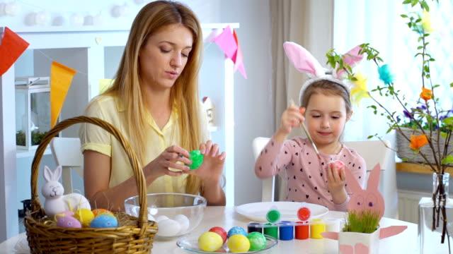 Frohe Ostern! Mutter und ihre kleine Tochter tragen lustige Hasenohren Ostereier färben – Video