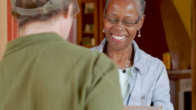 Happy elderly black woman receiving home delivery package delivery Happy smiling attractive elderly senior black woman receiving a home delivery package delivery box and signing electronic delivery device app from courier post office stock videos & royalty-free footage