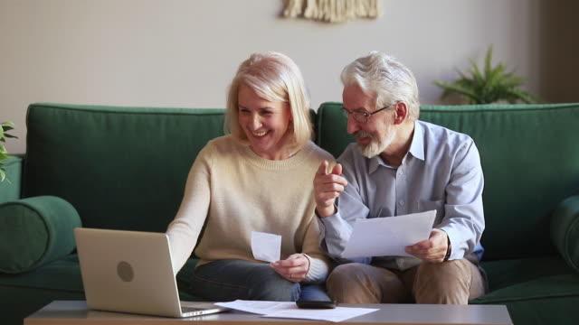 행복한 노인 부부는 온라인 전자 뱅킹을 사용하여 가족 예산을 관리합니다. - 검사 보기 스톡 비디오 및 b-롤 화면