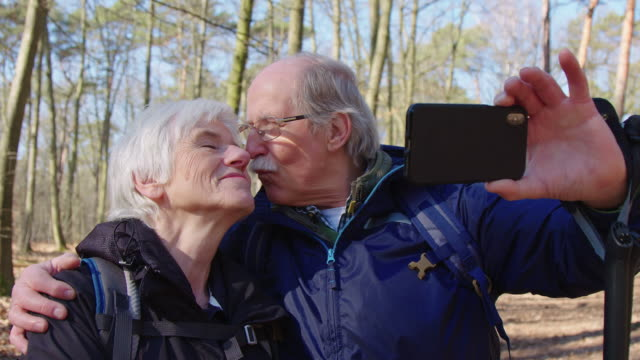 Happy elderly couple taking self portrait in trip