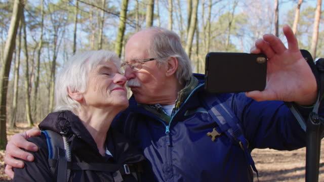 fröhliches älteres ehepaar, das sich in der reise selbst porträtiert - aktiver senior stock-videos und b-roll-filmmaterial