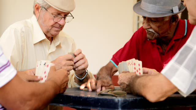 Happy Elderly Men Smiling Laughing Playing Cards At Home