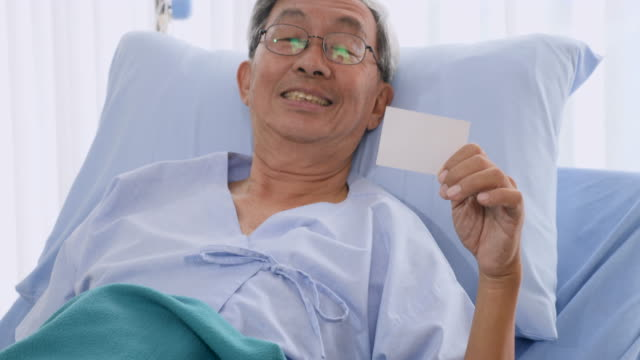 Happy elderly patient holding insurance card on bed at hospital video