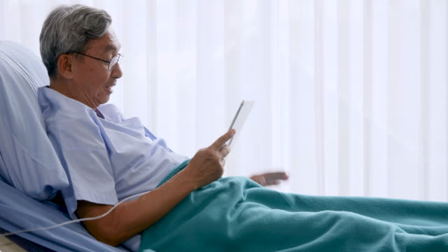Happy elderly patient sitting on bed and making video call with tablet at hospital video