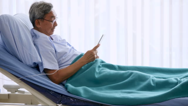 Happy elderly patient using tablet on bed at hospital video
