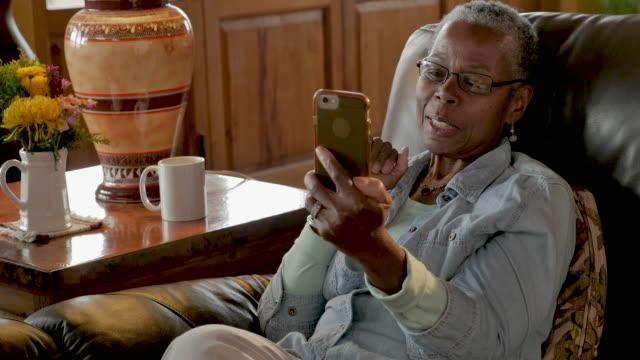 Happy elderly senior black woman  chatting on her mobile phone