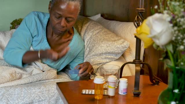 Happy elderly senior black woman taking her medicine and going to sleep