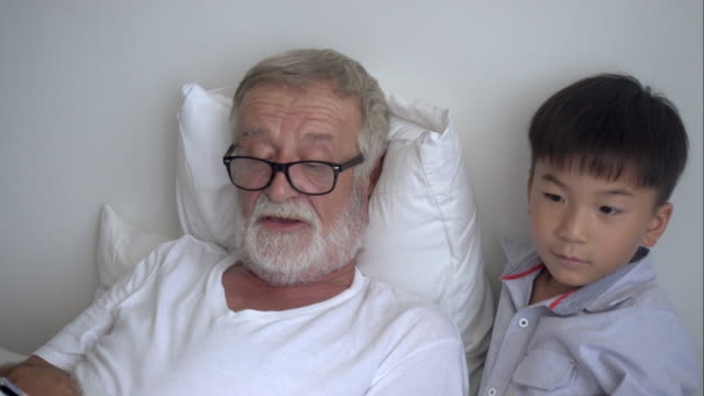 Happy elderly senior man grandfather telling story about play to boy grandson on bed at nursing home