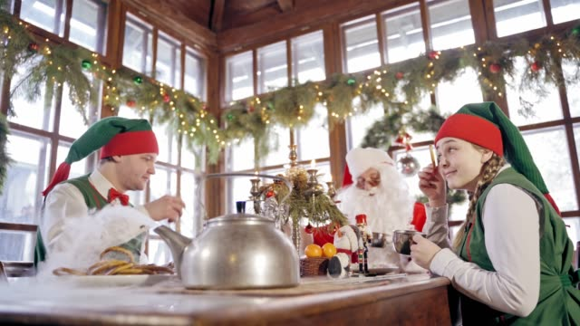 Happy elves and Santa at the table on Christmas decorations background.