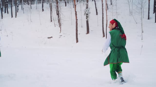 Happy elves in green costumes with big ears are playing with white snow in the forest.