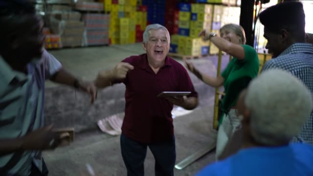 happy employees celebrating together at warehouse - prodotti supermercato video stock e b–roll