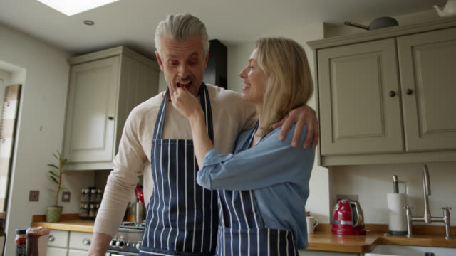 Happy English couple cooking together at home and wife feeding husband a bite