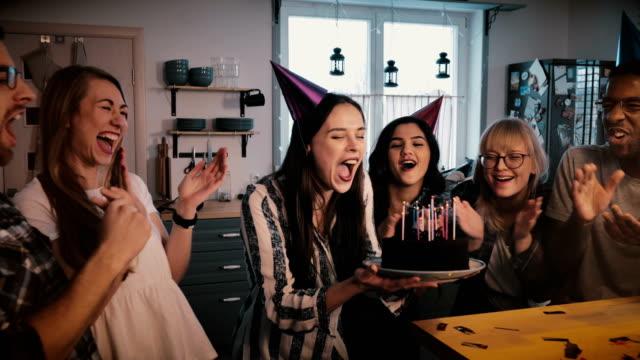 vídeos de stock, filmes e b-roll de garota feliz europeu detém o bolo de aniversário, sopra velas celebrando com amigos multiétnicas e câmera lenta de confete - soprando