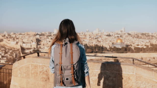 Happy European tourist female raises hands. Israel, Jerusalem. Girl with backpack walks to see old town panorama. 4K video