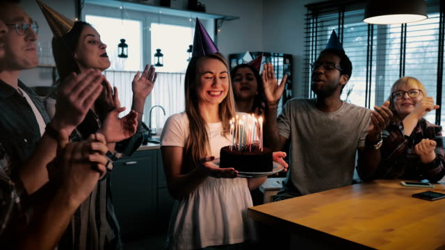 Happy excited Caucasian girl holding birthday cake, multiethnic friends sing a cheerful song at fun party slow motion Happy excited Caucasian girl holding birthday cake, multiethnic friends sing a cheerful song at fun party slow motion. Young people sharing family relationships, celebrate holiday together at home. happy birthday stock videos & royalty-free footage