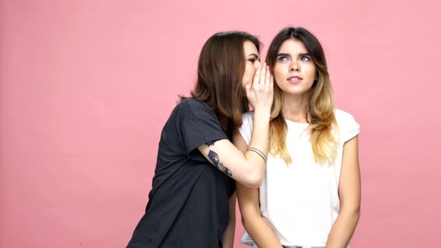 Happy excited girl whispering bad news to her female friend isolated over pink background