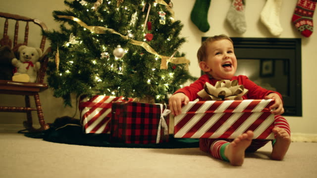 A Happy, Excited Three-Year Old Caucasian Boy Open a Christmas Present by the Christmas Tree on Christmas Day A Happy, Excited Three-Year Old Caucasian Boy Open a Christmas Present by the Christmas Tree on Christmas Day christmas stocking stock videos & royalty-free footage