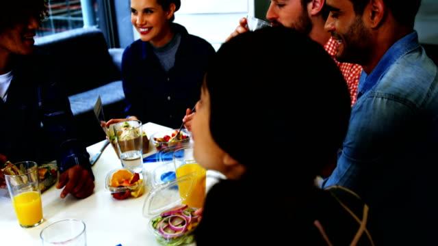 vidéos et rushes de cadres heureux interagir tout en prenant son petit déjeuner - pots de bureau