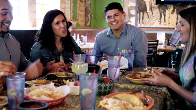 Happy extended Hispanic family having meal together in restaurant video