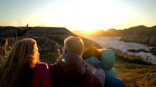 vídeos de stock e filmes b-roll de happy family admiring the sunset or sunrise on the rocky north shore of the sea - países nórdicos