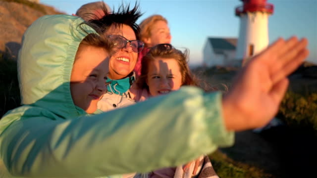vídeos de stock e filmes b-roll de happy family admiring the sunset or sunrise on the rocky north shore of the sea with an old lighthouse - noruega