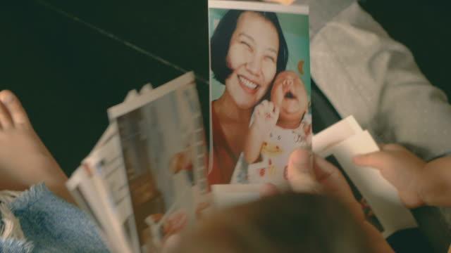 glückliche familie und fotoalbum - fotografisches bild stock-videos und b-roll-filmmaterial