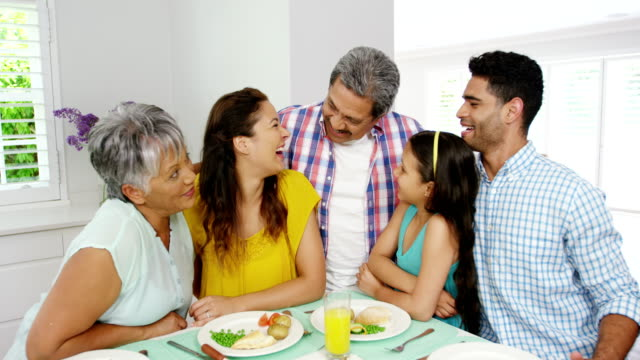 Happy family around dining table video