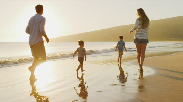 Happy family chasing each other on the beach