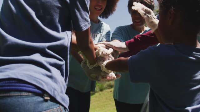 stockvideo's en b-roll-footage met gelukkige familie die een tuin samen schoonmaakt - huddle
