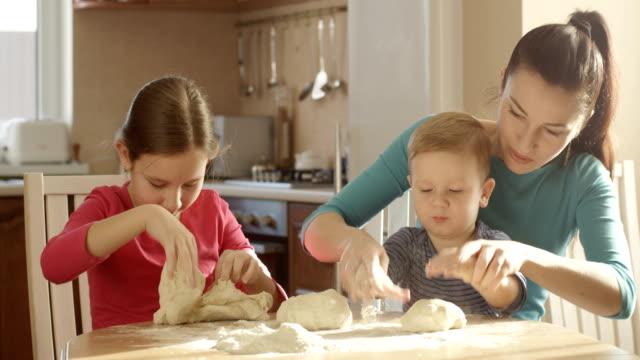 Glückliche Familie kochen in der Küche spielen mit dem Teig und Zutaten – Video