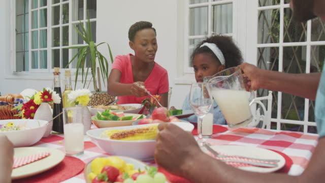 glückliche familie isst zusammen am tisch - vollzeit elternteil stock-videos und b-roll-filmmaterial