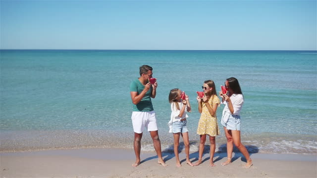 happy family eating watermelon on the beach. - eastern european descent stock videos & royalty-free footage