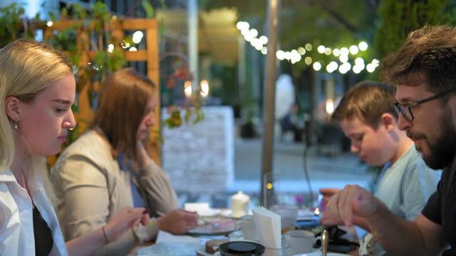 幸せな家族は、異なる料理でテーブルに座って寿司を食べます - パティオ点の映像素材/bロール