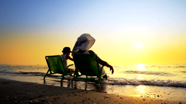 Happy family enjoy luxury sunset on the beach during summer vacations. Mother and son are sitting on a beach deck chair, against sunset, cinematic steadicam shot