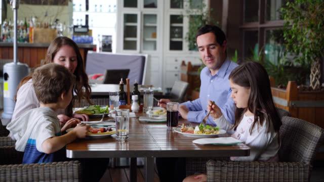stockvideo's en b-roll-footage met happy family geniet van een heerlijk ontbijt in het restaurant van het hotel praten en glimlachen - maaltijd