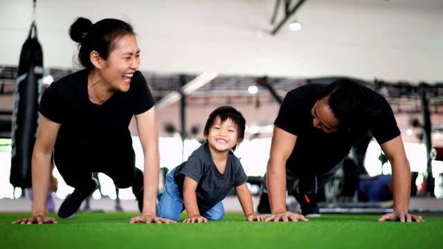 stockvideo's en b-roll-footage met slo mo - gelukkige familie genieten van doet push ups in sportschool - aziatische etniciteit