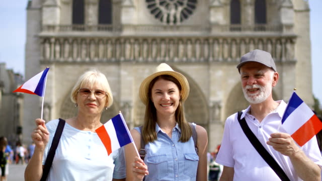 Happy family enjoying vacation. Seniors and their daughter near Notre Dame of Paris. Waving French flags video