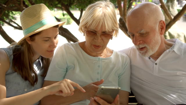 Happy family enjoying vacation. Seniors and their daughter sitting in park browsing in smartphone video