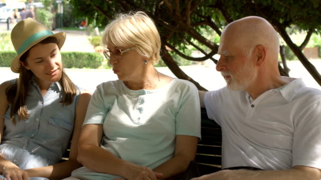 Happy family enjoying vacation. Seniors and their daughter sitting on bench in park relaxing video