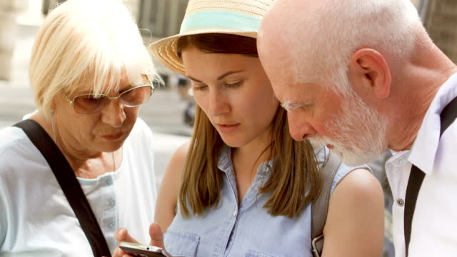Happy family enjoying vacation. Seniors and their daughter standing on street browsing in smartphone video
