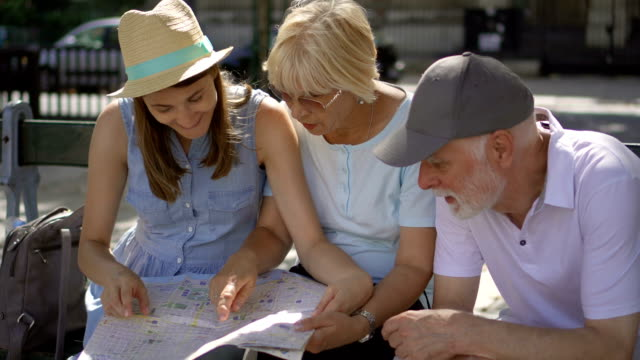 Happy family enjoying vacation. Seniors and their daughter studying city map looking for showplaces video