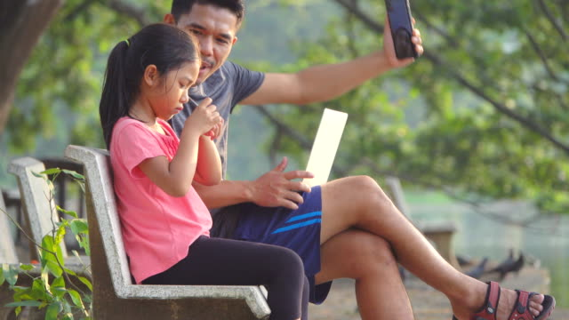 Happy family Father and Daughter using technologies sitting in the park