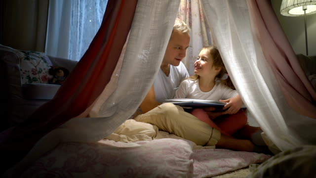 happy family father and her little daughter having fun reading a book in a tent at home. - fiaba video stock e b–roll