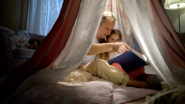 happy family father and her little daughter having fun reading a book in a tent at home. - family home video stock e b–roll